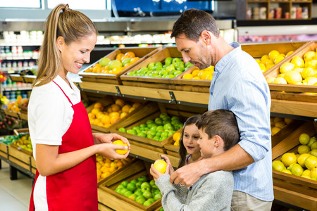 abarrotes: familia feliz de discutir con el trabajador en la tienda de comestibles