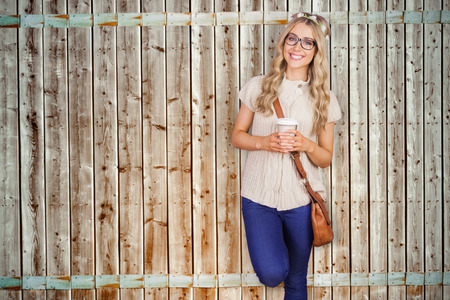 fade away: Gorgeous smiling blonde hipster leaning against red brick background against wooden background in pale wood Stock Photo