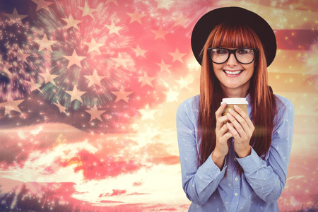 Smiling hipster woman drinking coffee against composite image of colourful fireworks exploding on black background Stock Photo