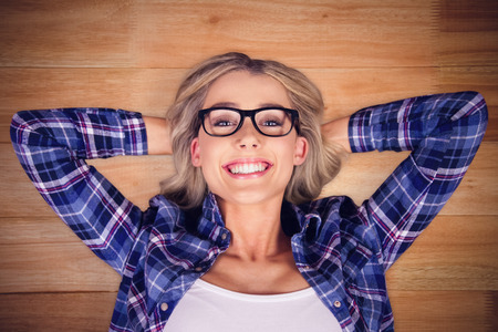 timber floor: Gorgeous smiling blonde hipster lying  against wooden flooring Stock Photo