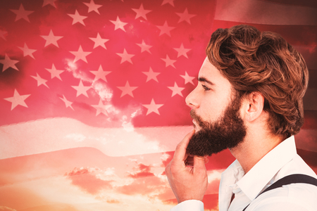 rippling: Profile view of hipster touching beard against american flag rippling against sunrise over mountains