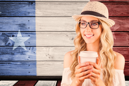 Gorgeous smiling blonde hipster holding take-away cup against composite image of usa national flag
