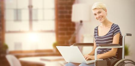 persona en silla de ruedas: Mujer en silla de ruedas que usa el ordenador portátil de escritorio en contra de las gafas y el bloc de notas Foto de archivo