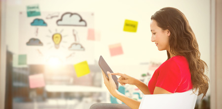 Woman sitting with tablet against adhesive notes on window Stock Photo