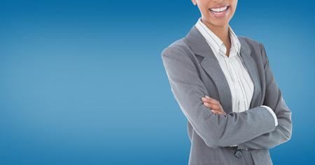 royal blue: Portrait of smiling businesswoman standing arms crossed against royal blue