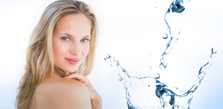 fresh water: Water bubbling on white surface against pretty blonde sitting on massage table Stock Photo