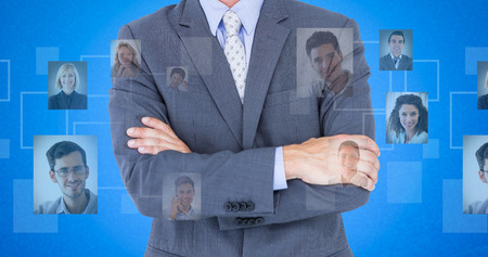 asia business: Portrait of smiling businessman standing arms crossed against blue background