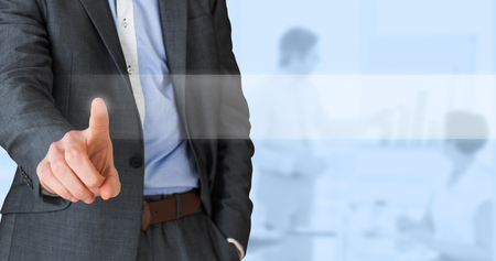 table: Businessman in grey suit pointing against blue background