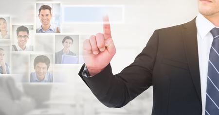 unsmiling: Unsmiling businessman pointing his finger against grey background