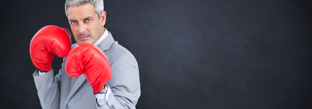 tough: Tough businessman with boxing gloves against blackboard