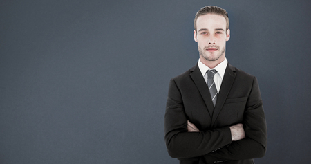 frowning: Frowning businessman looking at camera against grey background Stock Photo
