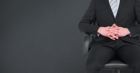 swivel chairs: Stern businessman sitting on an office chair against grey background