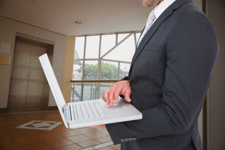 foyer: Businessman holding laptop against foyer area with elevator