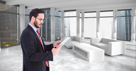 scrolling: Businessman scrolling on his digital tablet against modern room overlooking city