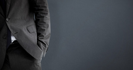 hand in pocket: Businessman standing with hand in pocket against grey background
