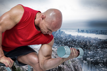 free weight: Bald man exercising with dumbbells while sitting on bench press against large rock overlooking huge city
