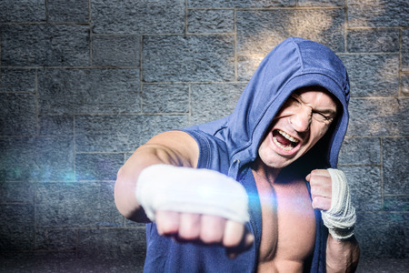punching: Aggressive fighter punching against black background against grey