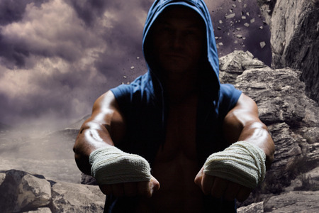 dark sky: Athlete in hood with bandage on hand against rock crashing down from cliff