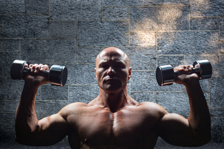 shaved head: Portrait of man exercising with dumbbells against grey