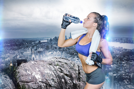 large rock: Fit woman drinking water against large rock overlooking huge city Stock Photo