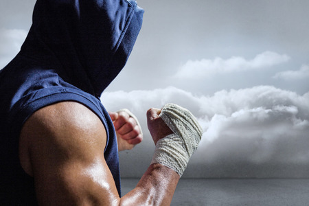 fighting stance: Muscular man in blue hood with fighting stance against clouds in a room