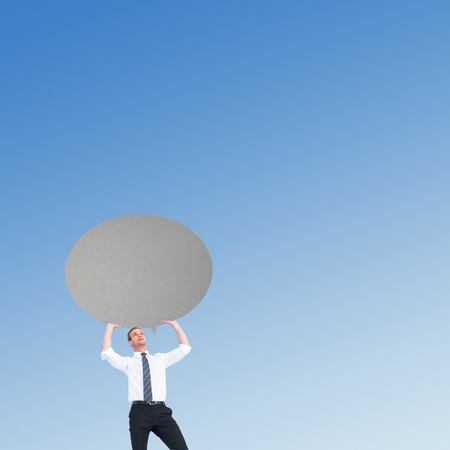 looking away: Businessman holding a speech bubble against blue sky