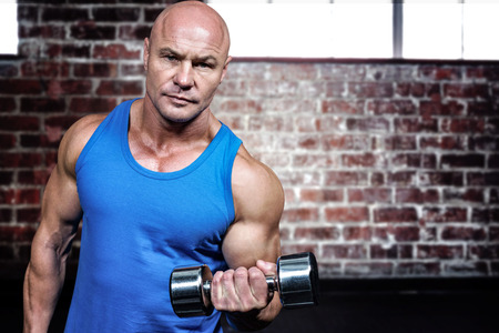 free weight: Portrait of man lifting dumbbells against gym Stock Photo