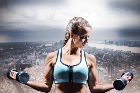 large rock: Sporty woman lifting dumbbells against large rock overlooking huge city