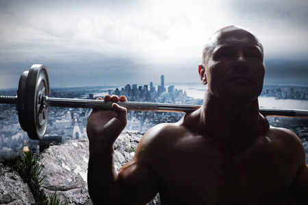 large rock: Muscular healthy man lifting crossfit against large rock overlooking huge city