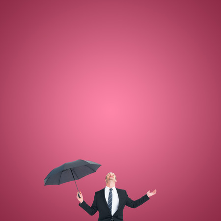 sheltering: Businessman sheltering under black umbrella testing against red vignette