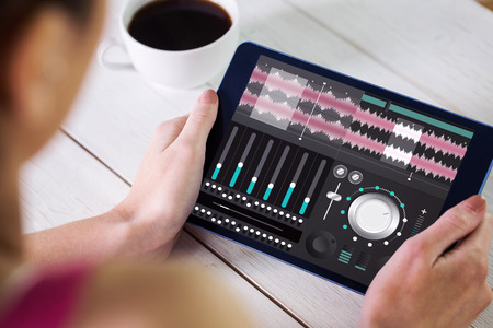 using tablet: Woman using tablet pc against music app Stock Photo