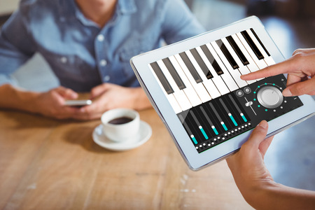 remix: Music app against person using tablet computer in cafe Stock Photo