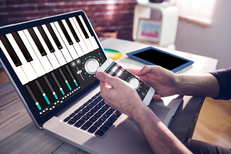 graphic designing: Music app against cropped hand of graphic designer using smartphone and laptop Stock Photo