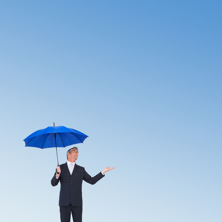 hand out: Businessman holding umbrella with hand out against blue sky