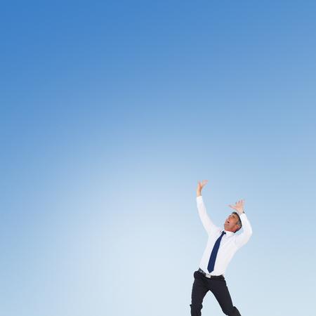 manos levantadas: Hombre de negocios con las manos levantadas sobre fondo blanco contra el cielo azul