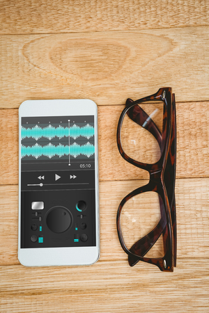 remix: Music app against view of glasses and a smartphone Stock Photo