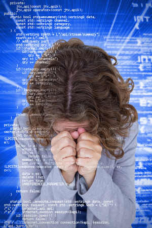 covering the face: Upset woman with hands covering face against blue background with coding Stock Photo