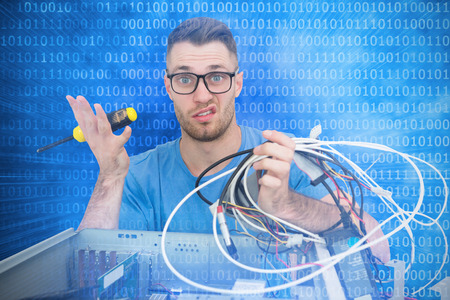 screw driver: Portrait of confused it professional with screw driver and cables in front of open cpu against glowing futuristic binary code
