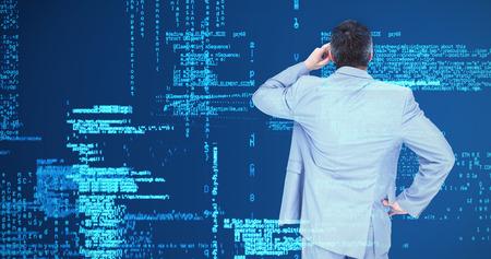businessman thinking: Thinking businessman against blue data Stock Photo
