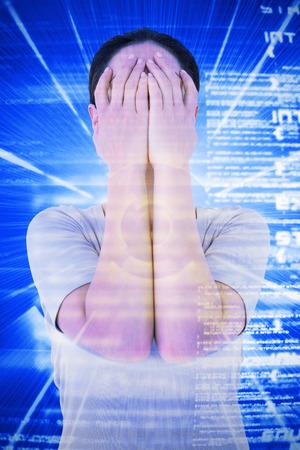 desolaci�n: Mujer triste que oculta su cara contra el fondo azul con la codificaci�n Foto de archivo