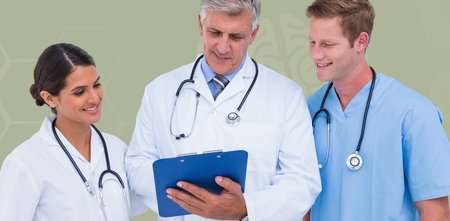 writing pad: Doctor working with colleagues while holding writing pad  against blue