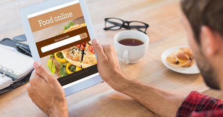 man rear view: Rear view of man using tablet on wooden table against food app
