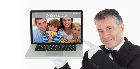Smiling waiter pointing us something on a laptop against food app photo