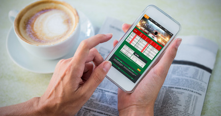 gambling: Gambling app screen against man using mobile phone by coffee and newspaper in cafe