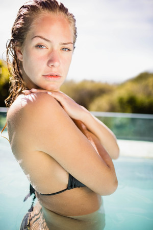 crossing arms: Unsmiling blonde in the pool crossing arms and looking at the camera