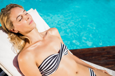 deckchair: Woman relaxing on deckchair by the pool