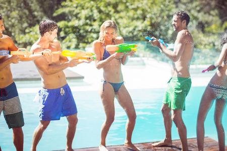 water gun: Happy friends doing water gun battle poolside Stock Photo