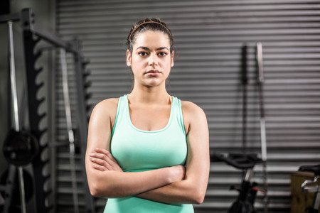 crossing arms: Unhappy athletic woman crossing arms at crossfit gym Stock Photo