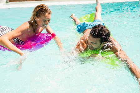 bikini couple: Happy couple on lilos splashing in the pool