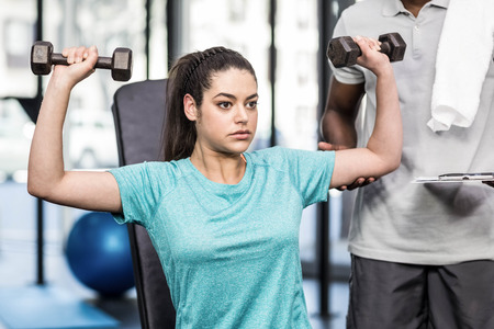 Athletic woman lifting weights helped by trainer at crossfit gym
